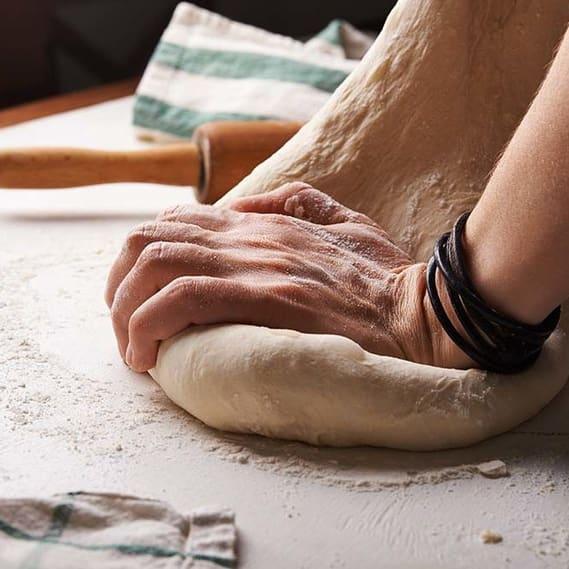 Hand mit frischem Teig in Bäckerei